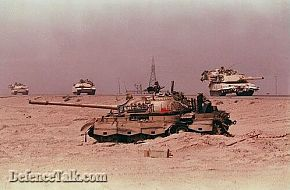 Abrams Tank in front of a destroyed T-72 Tank.