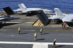 Sailors aboard aircraft carrier ready F/A-18 strike fighters