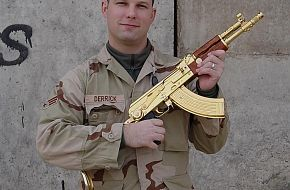 An american G.I (Marine or Army) poseign with Saddams AK-47.