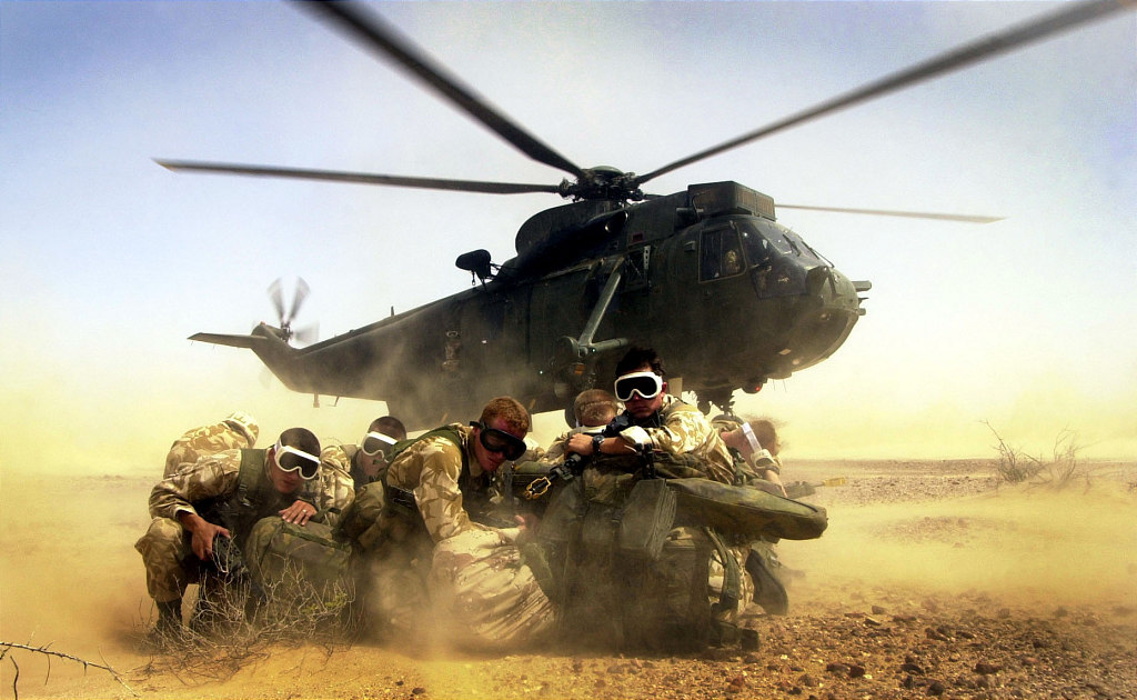 Royal Marines from 40 Commando go into a huddle as the Royal Navy Seaking h