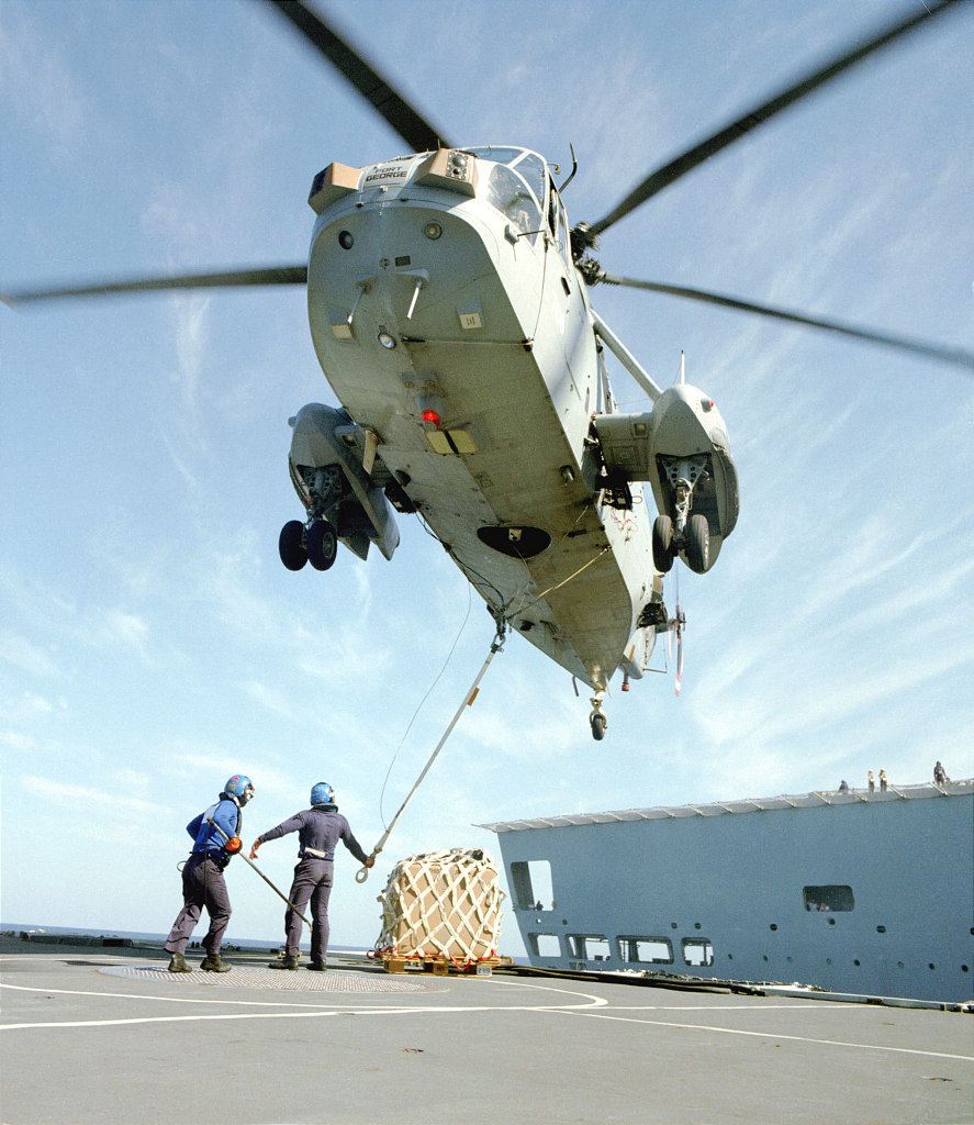 Sea King helicopter doing VERTREP (Vertical Replenishment at Sea).