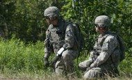 A First Army observer coach/trainer, right, and an officer with the Vermont Army National Guard's 86th Infantry Brigade Combat Team observe action during multi-echelon integrated brigade training on Fort Drum, N.Y., June 16, 2015.