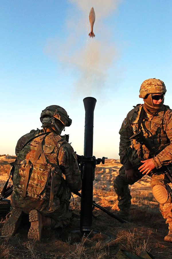 Pfc. Brady Barrett (right), an indirect fire infantryman assigned to Headquarters and Headquarters Troop, 3rd Squadron, 2nd Cavalry Regiment, turns away from an M252 mortar system after hanging an 81mm mortar round during a multinational mortar live-fire exercise alongside Latvian partners, Feb. 17, at Adazi Military Base, Latvia. Soldiers from both armies took turns rehearsing and executing a live fire scenario by reacting to enemy contact using direct and indirect fire in support of Operation Atlantic Resolve, a multinational demonstration of continued U.S. commitment to the collective security of North Atlantic Treaty Organization allies.