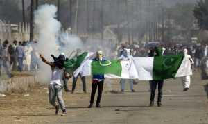 Masked Kashmiris hold the national flag of Pakistan during a protest